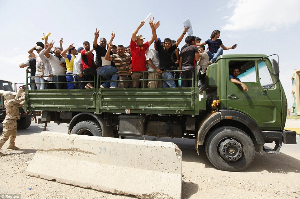 Volunteers who have joined the Iraqi Army to fight against the predominantly Sunni militants, who have taken over Mosul and other Northern provinces, gesture from an army truck