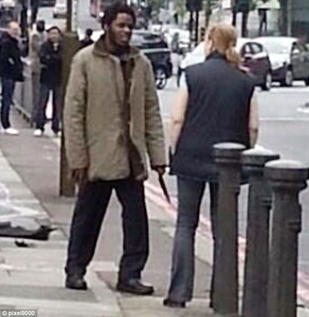 Troubled: The mother of Michael Adebowale, 22, desperately attempted to turn him against extremism. He is pictured with a knife in his hand at the scene where Lee Rigby was stabbed to death