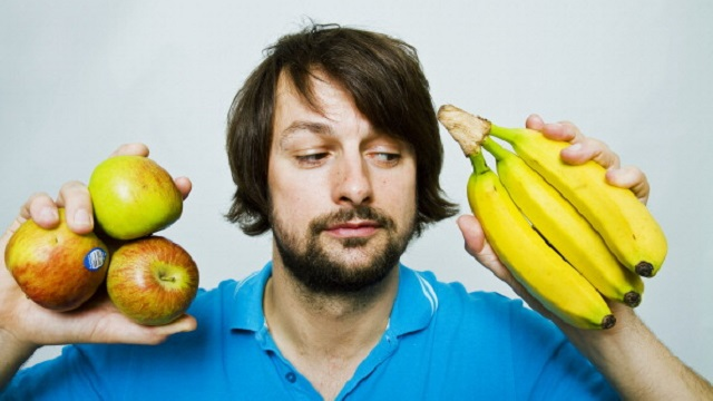 Man deciding whether to eat apple or banana