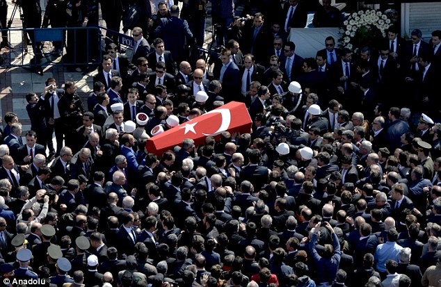 Mourning: The coffin of the prosecutor was passed through the crowds of mourners gathered to pay their respects. He had been leading an investigation into the death of teenagerBerkin Elvan, who died aged 15
