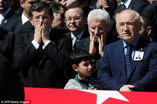 Respects: Turkish Prime Minister Ahmet Davutoglu (L), the son of killed prosecutor Mehmet Selim Kiraz (C) and Turkish National Assembly President Cemil Cicek (R) stand by Kiraz' coffin in Istanbul