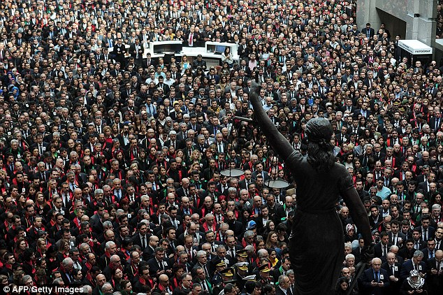 Gathering: Prosecutors, lawyers and judges stand near a statue of Lady Justice during the funeral ceremony