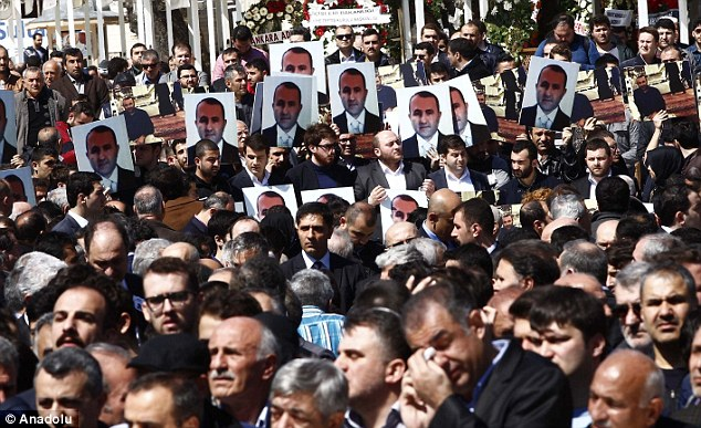 Defiant: Mourners at the funeral of Kiraz hold a picture of the prosecutor high in tribute to the lawyer
