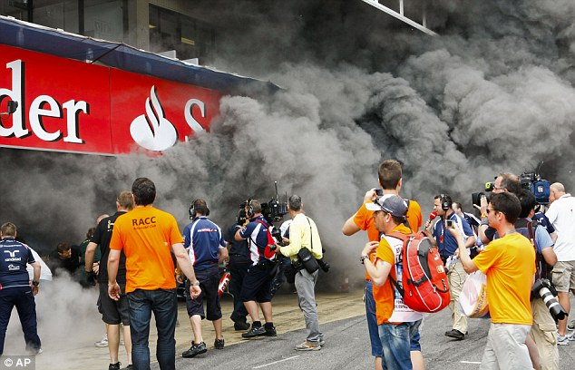 Crisis: The pit-lane is engulfed in smoke as a Caterham team member lies on the ground (below)