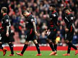 Raheem Sterling  of Liverpool (1st from L)  leaves the pitch with team mates looking dejected after the final whistle