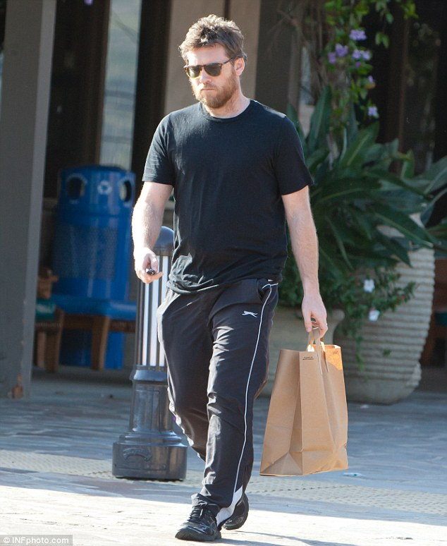 In nesting mode: The new dad sported a decent beard and scruffy hair, wearing tracksuit pants and trainers for the outing