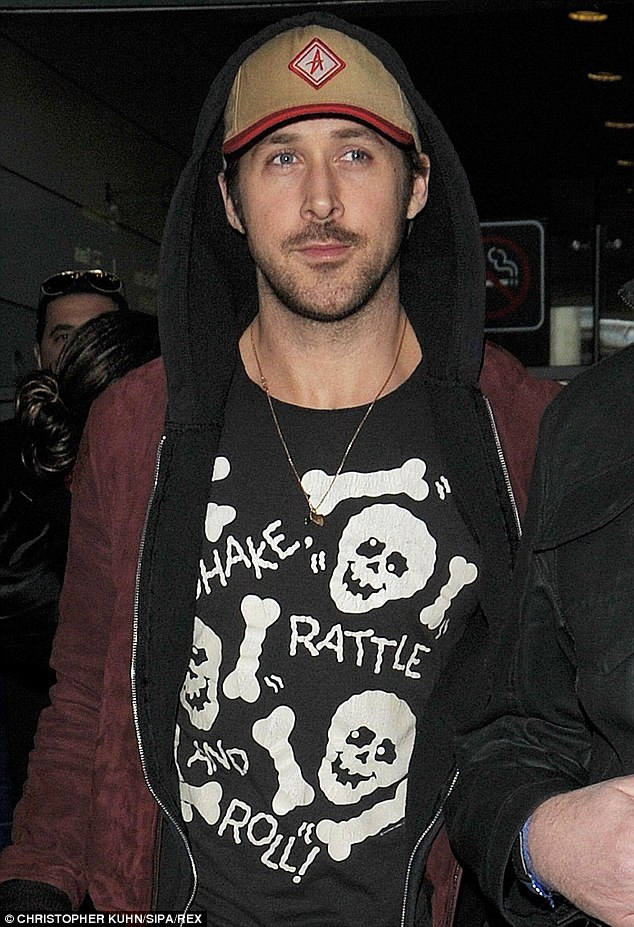 Cool: He travelled in a stylish red suede jacket over a black hoodie, which he teamed with a tan cap