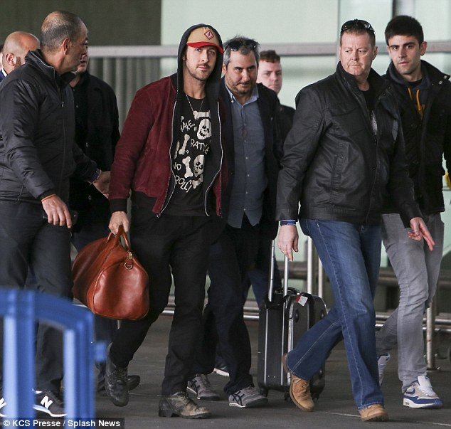 Flanked: The actor was flanked by a team of handlers as he made his way through the busy terminal