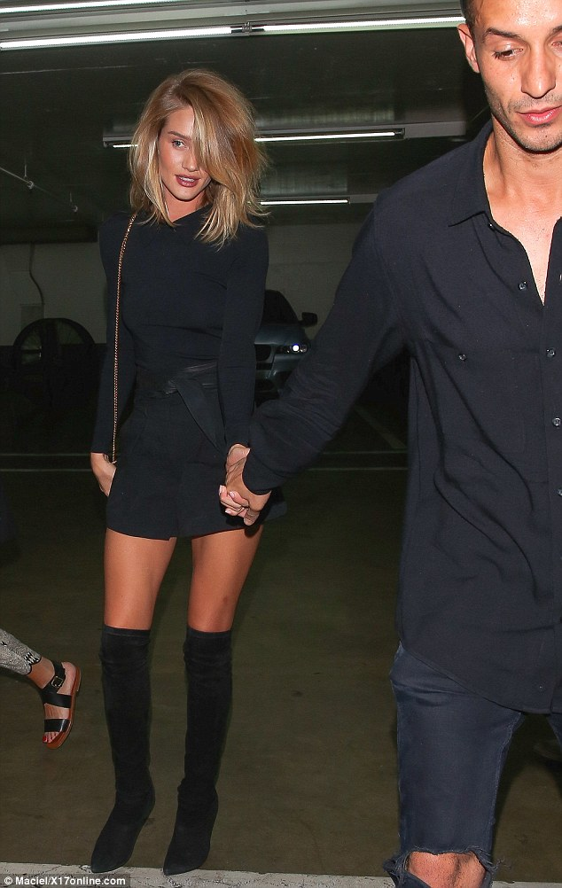 Party-time: Rosie looked stunning as she was helped by a male-friend from a nightclub where she had been enjoying herself with Orlando Bloom on Saturday night
