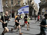 An athlete runs with an Israeli flag during the fifth international Jerusalem Marathon, March 13, 2015. Over 20,000 runners from some 60 countries took part in the annual sporting event on Friday, with tracks passing near the Old City, one of Jerusalem's most well-known sites. The event included full and half marathon tracks, as well as a 10km and 5km race and a16km hand-cycle race. REUTERS/Ammar Awad (JERUSALEM - Tags: SPORT ATHLETICS) - RTR4T7M2