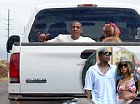 """EXCLUSIVE: **NO WEB** Aloha! They're used to private jets and fancy escalades but Jay Z and Beyoncé seemed happy travelling local style on their secret vacation to Hawaii. Flashing a rare smile and a """"hang loose"""" shaka hand sign the rap mogul, 45, slouched down next to Queen B, 33, who had a garland of flowers in her hair. The power couple appeared to be enjoying the warm Pacific breeze when they were spotted hitching a ride in the back of this open-top truck at about 2.30pm on April 7th 2015. Their daughter Blue Ivy Carter was nowhere to be seen.  A local man spoke with the American music icons as he snapped their picture. """"I talked to them for a moment and Beyoncé gave the shaka sign too,"""" said the source, who noted that the couple were wearing matching white t-shirts. """"After that Beyoncé didn't turn around much on the ride, but Jay Z was facing the road smiling and drinking what looked like a beer from a cooler in the back of the pickup¿they were really chill,' he added. The couple"""