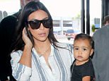 UK CLIENTS MUST CREDIT: AKM-GSI ONLY\nKim Kardashian, Kanye and North West arrive at LAX to catch a departing flight. Little North looked super cute, matching her monochromatic tones with her leather boots and YSL designer mini-bag. Her mom kept it simple in a striped dress shirt, white skinny trousers and gladiator style booties.\n\nPictured: Kim Kardashian and North West\nRef: SPL832274  010914  \nPicture by: AKM-GSI / Splash News\n\n