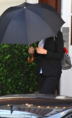 Protection: The 42-year-old kept herself hidden from the sun's rays in the short walk from the restaurant to her car under an umbrella