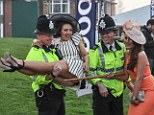 Catching a lift: One opportunistic female race-goer was pictured stretched out in the arms of a police officer at the end of Ladies' Day