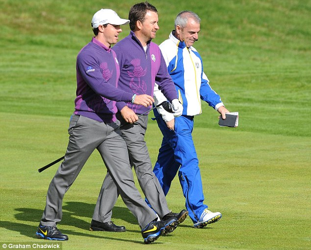 McGinley walks with Graeme McDowell and McIlroy as they prepared for the 2014 Ryder Cup