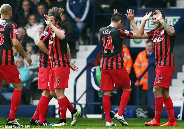 QPR celebrate the second of their four goals against West Brom from Charle Austin (right)