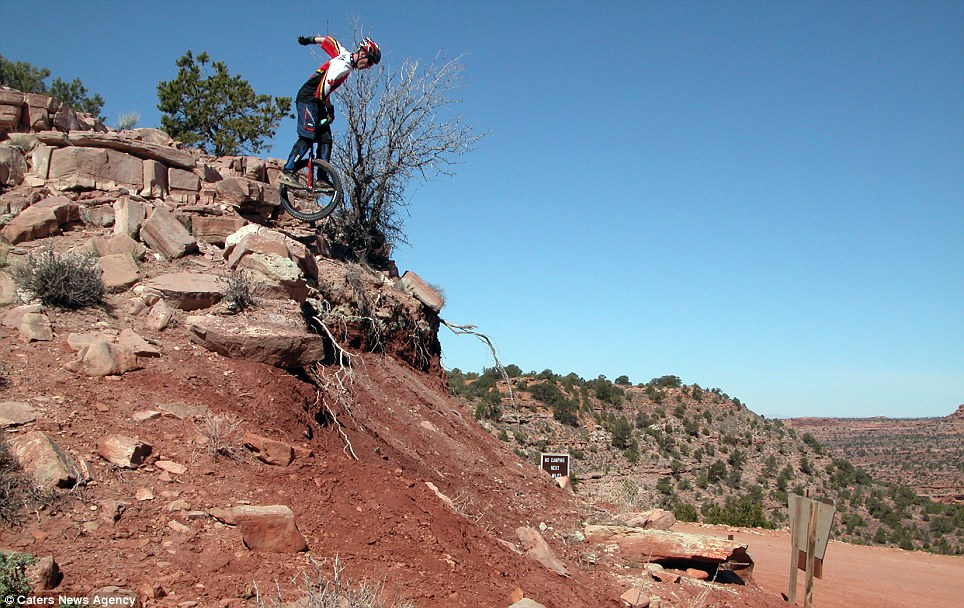 Leap of faith: Mr Holm fearlessly drops from a rock in sun-baked Utah