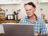 Older man using laptop in kitchen --- Image by © Dan Brownsword/cultura/Corbis