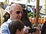 """Rome, Italy. 14th April 2015 -- Amazon founder and CEO, Jeff Bezos, takes photos in Rome's central """"Campo de' Fiori"""" market. -- Amazon.com founder and CEO Jeff Bezos, who has a net worth of some 34.7 billion dollars, was seen calmly walking around Romeís central ìCampo deí Fioriî market square, one of the Eternal Cityís more colorful outdoor markets."""
