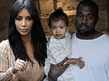 US rapper Kanye West, husband of US reality TV star Kim Kardashian, carries their daughter North, following a reported baptism ceremony at the Armenian St. James Cathedral in Jerusalem's Old City on April 13, 2015.  AFP PHOTO / AHMAD GHARABLIAHMAD GHARABLI/AFP/Getty Images