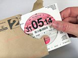 Opening an envelope containing a new UK road/car tax discs (UK car).