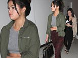 Selena Gomez goes undercover at LAX in a midriff and high-waisted paints as she catches a flight out of Los Angeles.  The adorable singer/actress was seen at LAX with black boots & bag, with an army green jacket & red pants.\n\nPictured: Selena Gomez\nRef: SPL999435  140415  \nPicture by: Splash News\n\nSplash News and Pictures\nLos Angeles: 310-821-2666\nNew York: 212-619-2666\nLondon: 870-934-2666\nphotodesk@splashnews.com\n