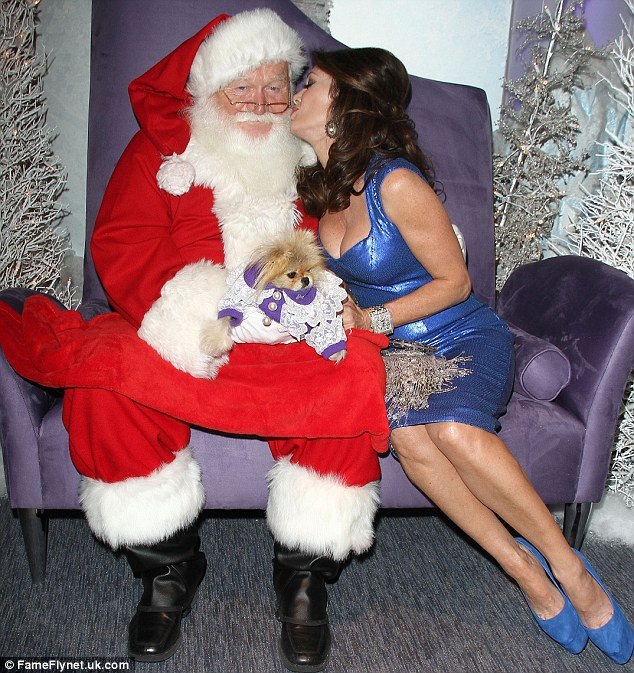 Patience of a saint: Santa managed to keep his eyes looking ahead as Lisa Vanderpump leaned in to kiss him at a pet portrait event in Los Angeles on Thursday