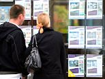 A stock photo of a couple looking for houses in estate agents window.