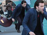 """*NO NEW YORK POST / NEW YORK DAILY NEWS / NEWSCOM* EXCLUSIVE: David Tennant is shot while sitting at a table at The Coffee Shop in Union Square while looking over a package of photographs by a hit man who fires a blank gun from inside a paper bag in a scene from """"A.K.A. Jessica Jones"""", a Netflix series. David grabs his neck, drops the package of photos, knocking over the table and stumbles, falling toward the ground as the director yelled """"cut.""""  Pictured: David Tennant Ref: SPL1005624  210415   EXCLUSIVE Picture by: Lawrence Schwartzwald  Splash News and Pictures Los Angeles: 310-821-2666 New York: 212-619-2666 London: 870-934-2666 photodesk@splashnews.com"""