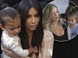 Kim Kardashian, a US reality TV star, carries her daughter North West as they arrive to a church in Jerusalem, Monday, April 12, 2015. Kim Kardashian, along with husband West, their daughter, North West, and her sister, Khloe, arrived to Israel on a private visit. (AP Photo/Olivier Fitoussi)