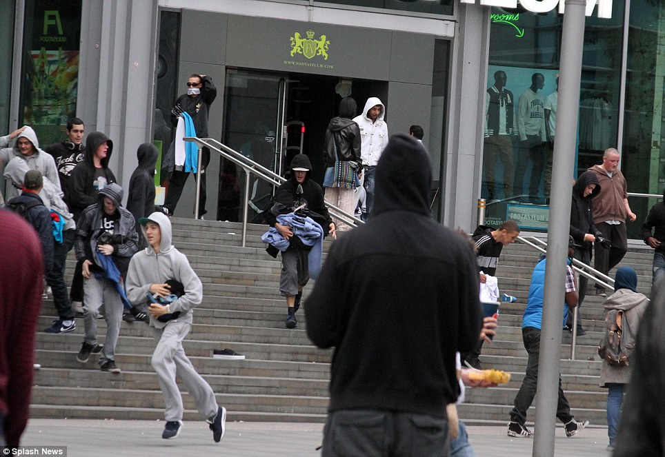 Manchester: Hooded looters with arm fulls of clothes run from a Manchester shopping centre yesterday evening