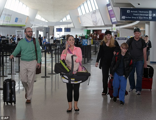 "Passengers arriving at Buffalo Niagara International Airport react to the group of media gathered to report on a SkyWest Airlines plane that made an emergency landing after one passenger aboard Flight 5622 lost consciousness and the pilots rapidly descended ""out of an abundance of caution."""