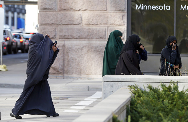 Members of Minnesota's Somali community cover their faces as they arrive at the St Paul court on Thursday