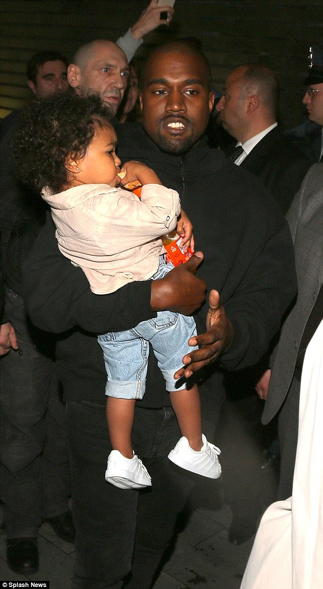Daddy duties: Kanye seemed refreshed after the flight as he carried sleepy North in his arms