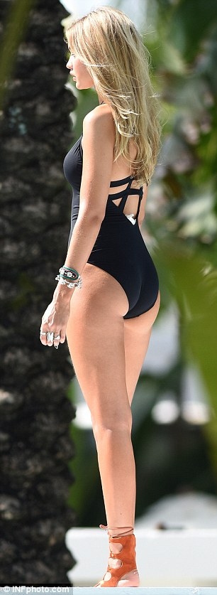 Her sexiest look: Gigi sizzled in a black plunging swimsuit with racy cut-out sections
