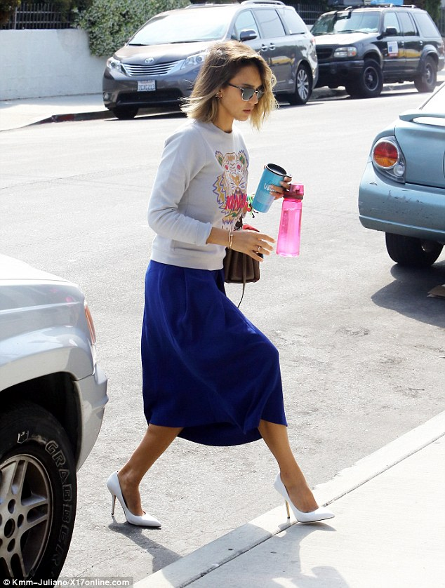 Step up: The flowing blue skirt allows the actress to walk freely across the street while her high heels may require a bit more attention to conquering the curb
