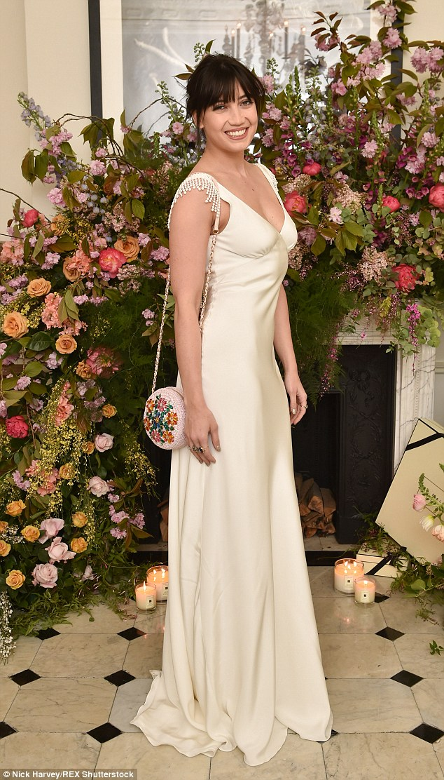Floral fancy: Daisy's shoulder bag matched the beautiful Scarlet & Violet blooms on display around the room