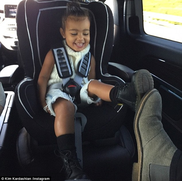The sweetest thing: Kim Kardashian posted an adorable throwback picture of her daughter North West, kicking up her legs and giggling while playing 'footsie' with Kanye West