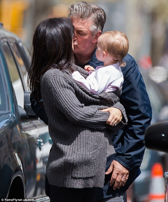 Loving it: Hilaria Baldwin locked lips with her husband Alec as they ran errands with their daughter Carmen in New York City on Wednesday