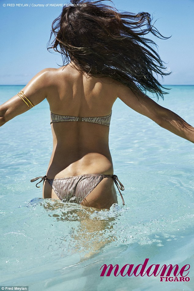And from the back...: Another picture - taken by famed photographer for the French fashion publication Fred Meylan - shows the star flaunting her honeyed skin in another bikini while in the ocean