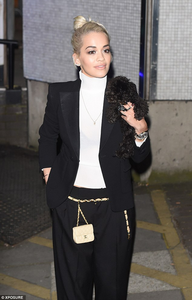 Puppy love: The singer poses for pictures outside ITV Studios with her beloved pet dog, who travels with her in a designer basket