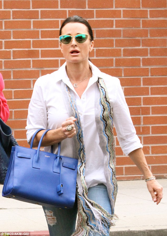 Dressed for success: her handbag and scarf combination complemented the simplicity of her white shirt and jeans ensemble
