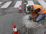 Jim Bachor scrapes away the cement to reveal his finished mosaic on a filled pothole in a Chicago street