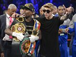 Floyd Mayweather Jr., left, poses for photos with Justin Bieber after defeating Canelo Alvarez during a 152-pound title fight, Saturday, Sept. 14, 2013, in Las Vegas.    (AP Photo/Mark J. Terrill)