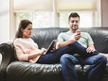 EBHEB2 Couple using digital tablet and smartphone on sofa