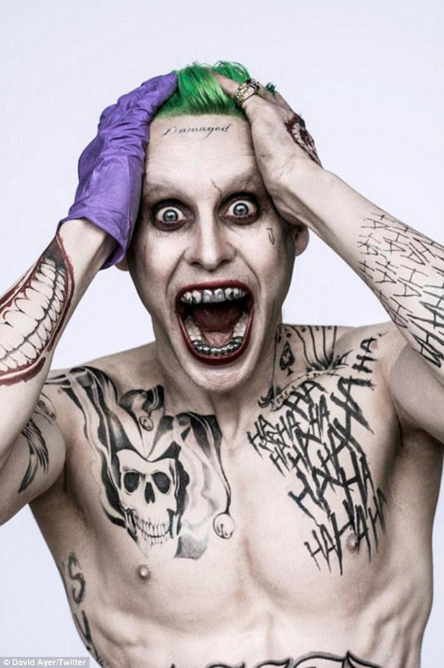Rocking a single purple glove: In it, the 43-year-old Oscar winner flashes his silver-capped teeth and full-body Joker ink, including the word 'damaged' across his forehead