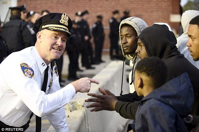 Captain Erik Pecha of the Baltimore Police Department exchanges words with young demonstrators