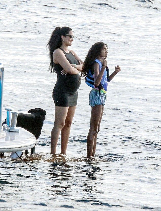 Relaxing: On vacation in Saint-Barts, the mother-of-four stands with her second oldest, Aoki looking out at the water