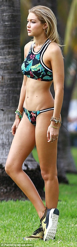 Laid-back: The blonde beauty's beach look was accessorized with a pair of green Nike sneakers