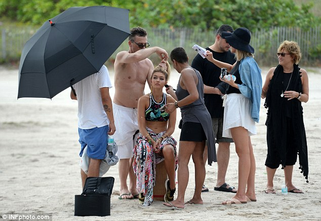 A little help from her friends: A glam squad attended the star before she was seen switching into another bathing suit design